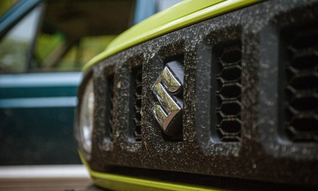 Suzuki Jimny : calandre et logo dans la forêt